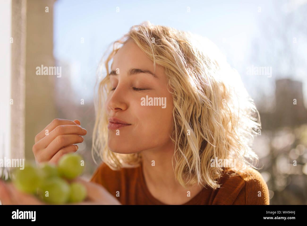 Ritratto di giovane donna bionda mangiare uva verde Foto Stock