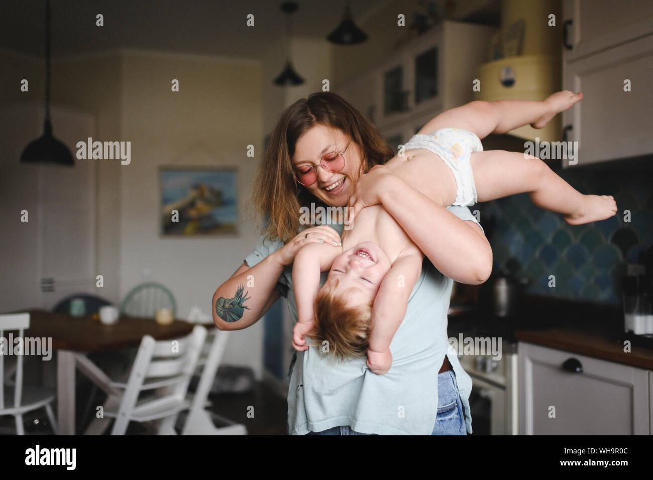 Ritratto di Madre gioca con il suo piccolo figlio in cucina Foto Stock