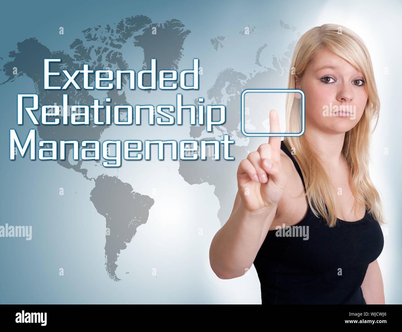 Giovane donna premere digital Extended Relationship Management sul pulsante di interfaccia nella parte anteriore della sua Foto Stock
