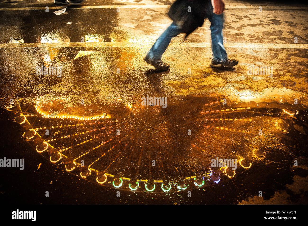 Sezione bassa dell uomo a camminare sulla strada bagnata di notte Foto Stock