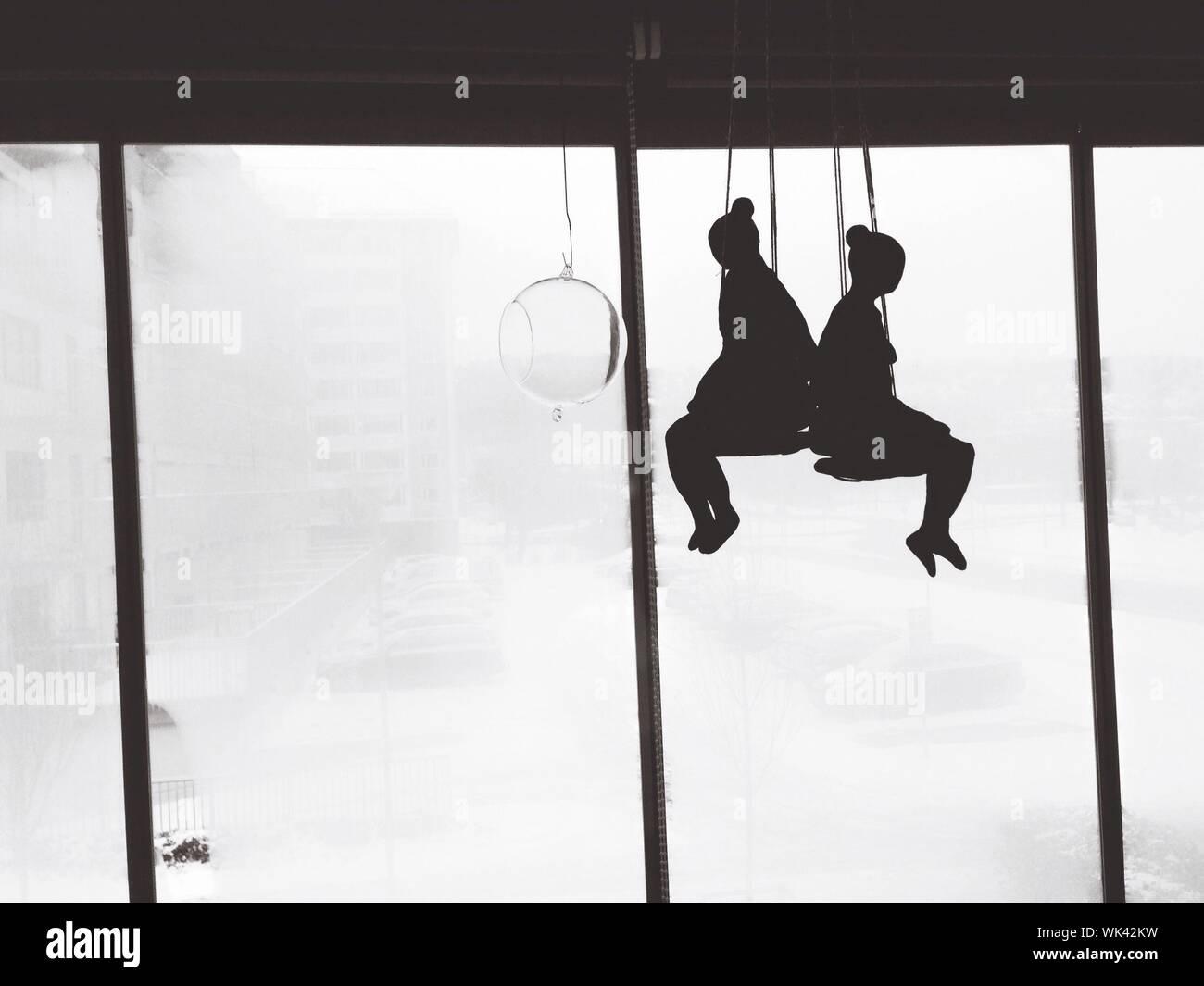 Silhouette di donna seduta su Swing contro la porta di vetro Foto Stock