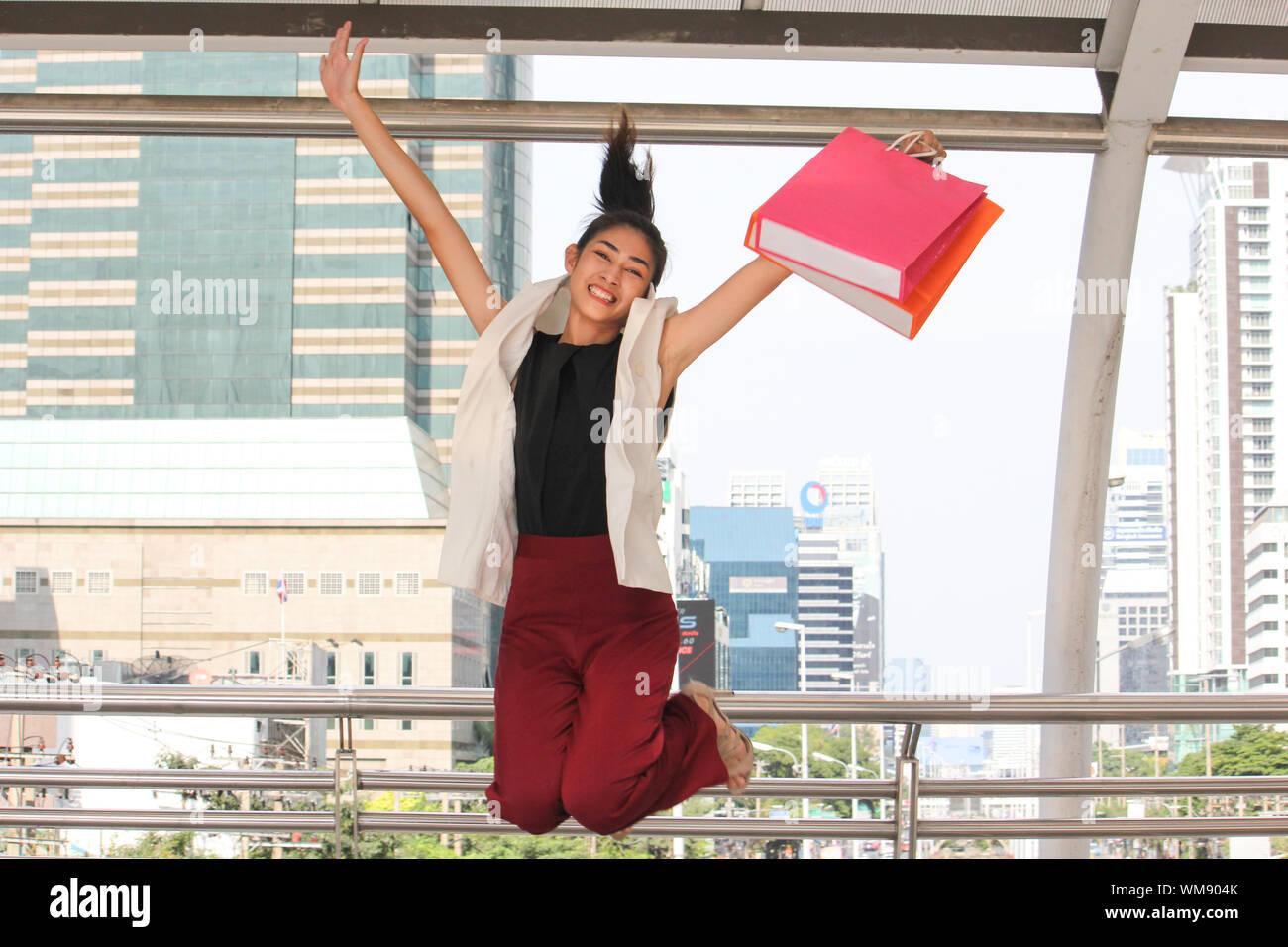 Ritratto di sorridente giovane donna con le borse della spesa il salto nel ponte di coperta Foto Stock
