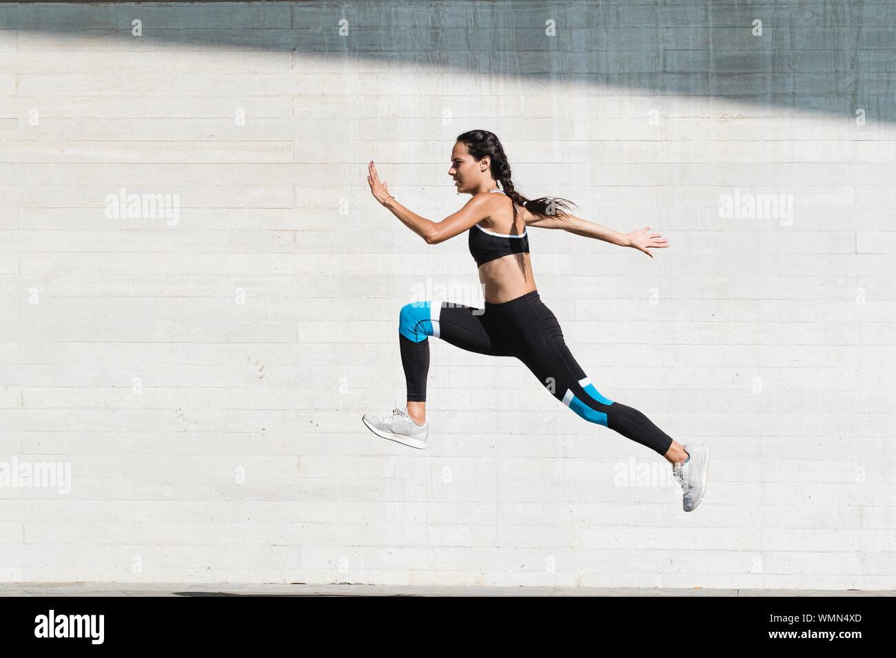 Corpo pieno di atleta femminile in sportswear saltando su calcestruzzo Foto Stock