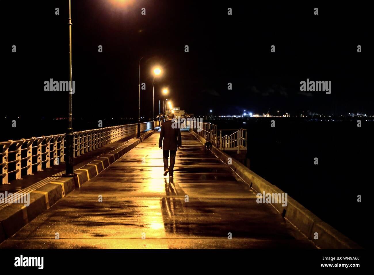 Vista posteriore del uomo a camminare sul bagnato illuminato Pier contro il cielo di notte Foto Stock