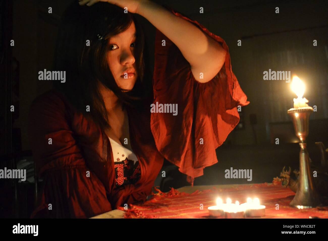 Ritratto di donna con candela accesa nella camera oscura Foto Stock