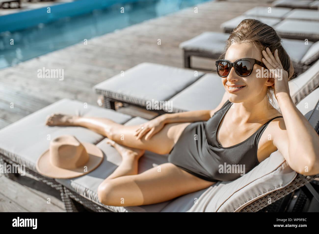 Donna in costume nero sdraiato sul lettino vicino alla piscina all'aperto. prendere il sole su un tempo di estate Foto Stock