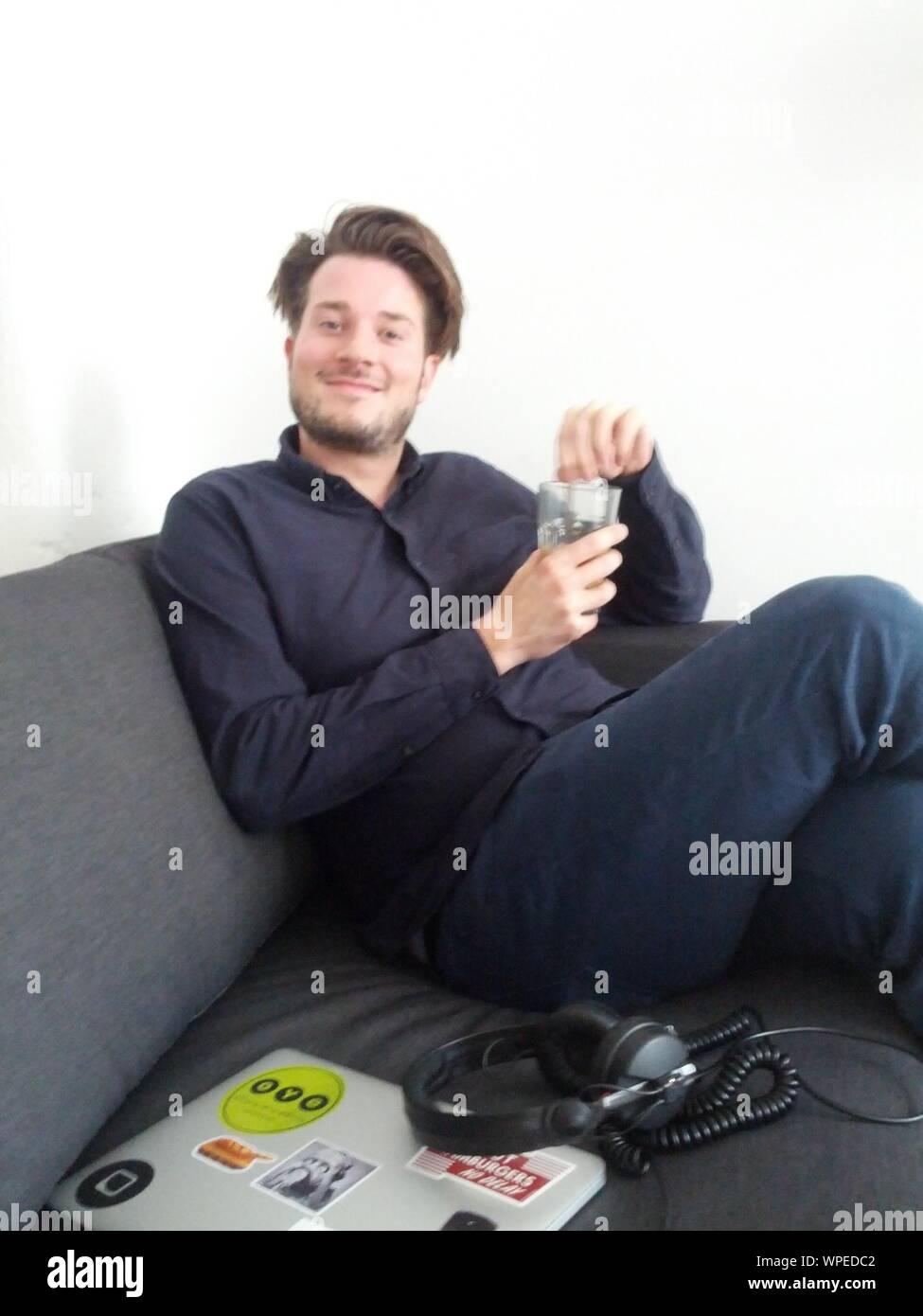 Ritratto di un giovane uomo seduto sul divano di casa Foto Stock