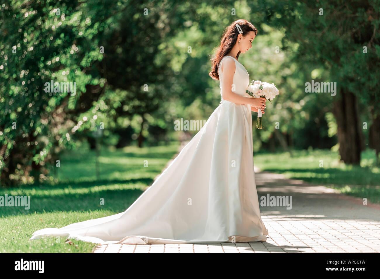 Bella giovane donna in abito da sposa in piedi nel parco. Foto Stock