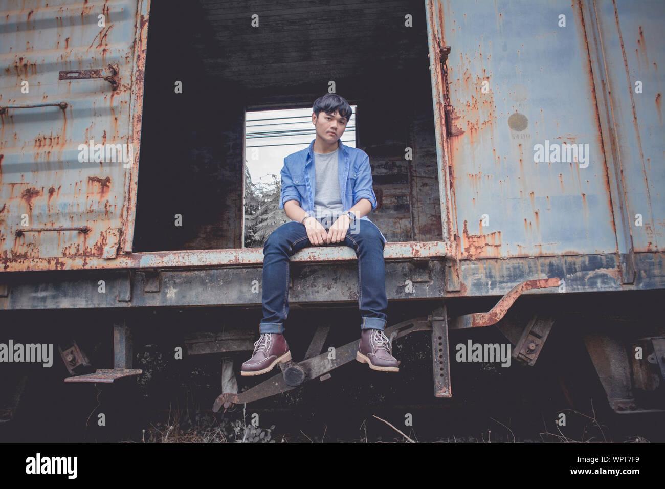 Angolo basso ritratto di Giovane triste seduto su abbandonato treno merci Foto Stock