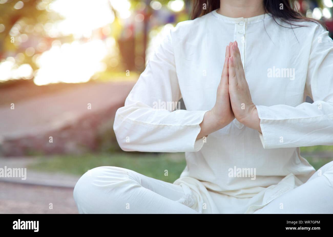 Close up della donna le mani in namaste. La meditazione sullo sfondo del tempio e la natura. Corsi di yoga in un centro di ritiri. Foto Stock