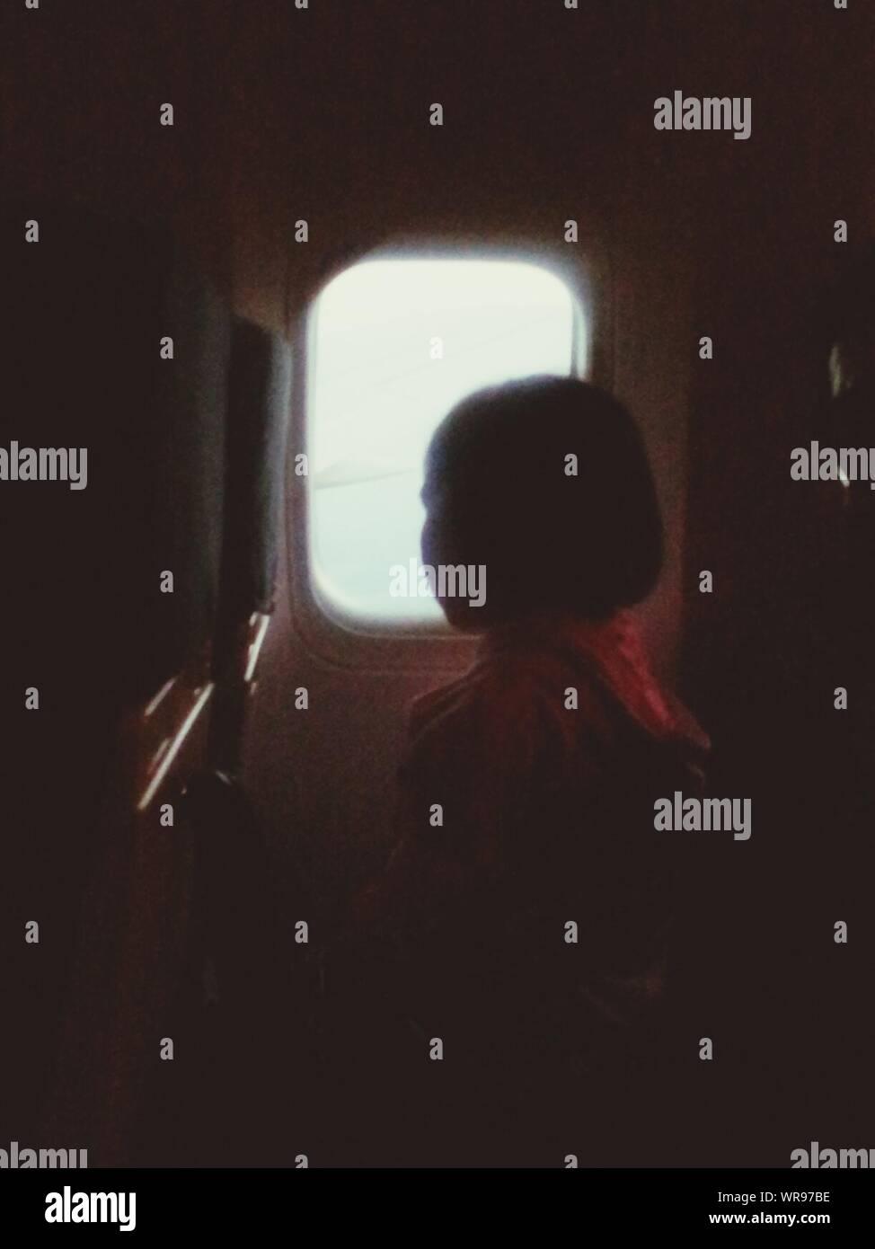 Giovane ragazza a guardare fuori dalla finestra di aeroplano Foto Stock
