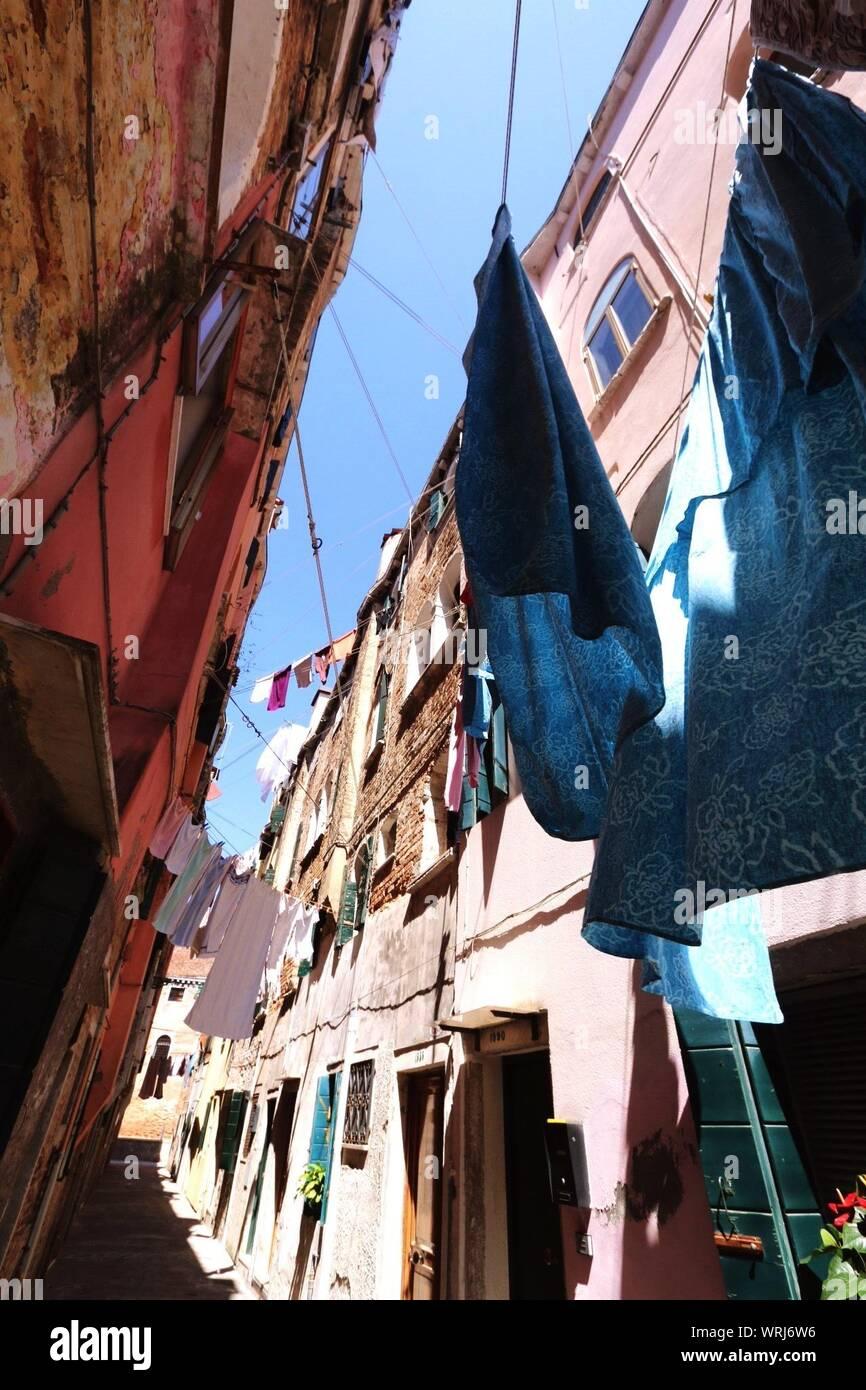 Servizio lavanderia appeso nella strada stretta Foto Stock