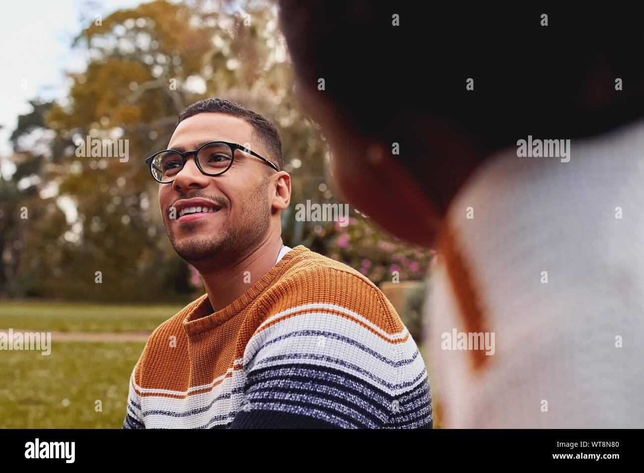 Close-up di un sorridente giovane africano indossando occhiali seduto con la sua fidanzata a park Foto Stock