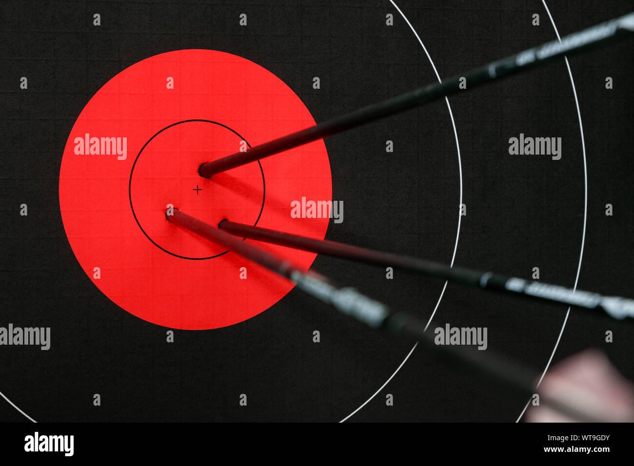 Tre frecce nel centro del rosso e del nero bersaglio tiro con l'arco. Accuratezza e precisione del concetto. Foto Stock