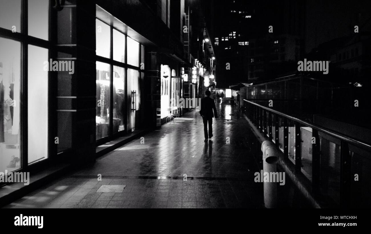 Lunghezza piena vista posteriore dell uomo a camminare sulla strada bagnata da edifici di notte Foto Stock