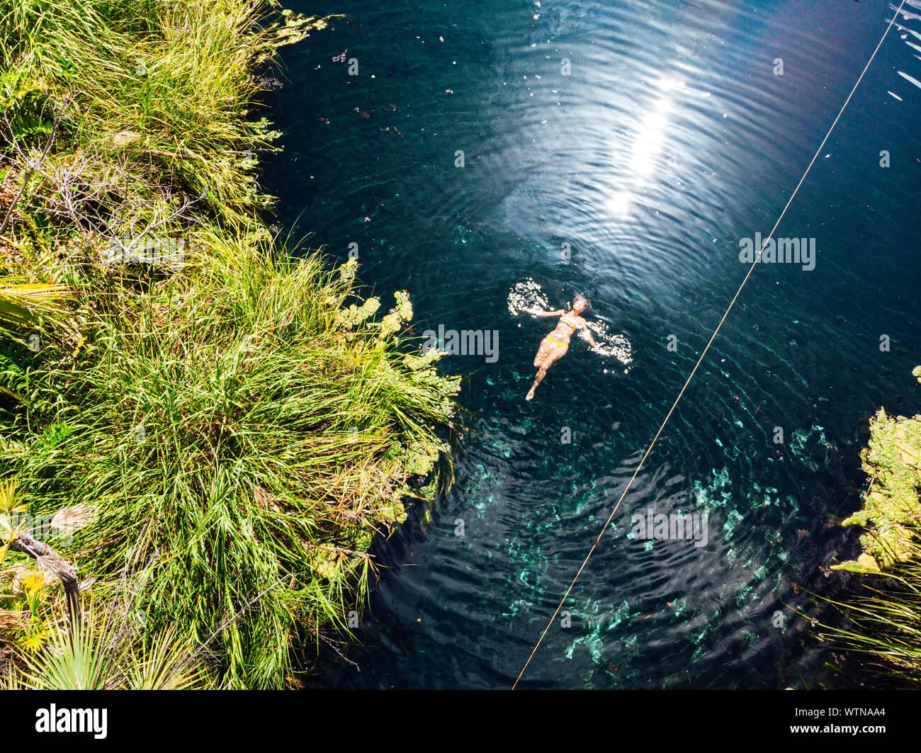 La donna a nuotare in acqua pulita del Cenote Crystal Foto Stock