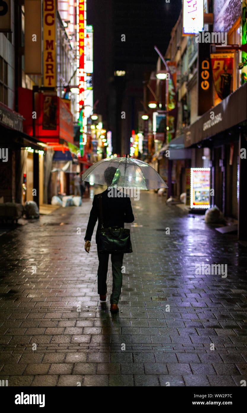 Uomo che cammina sotto la pioggia con ombrello di notte Foto Stock