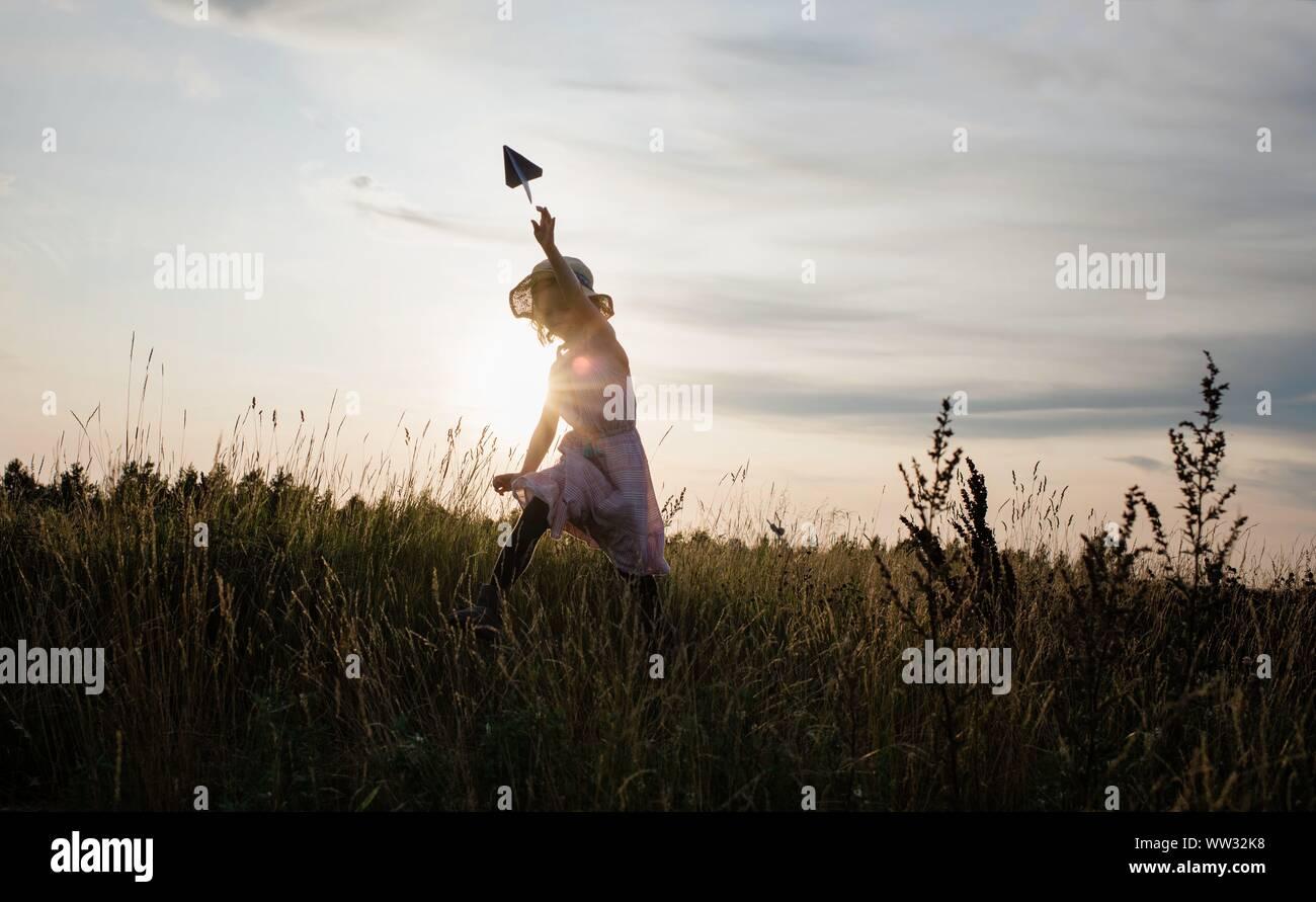 Ragazza a caccia di un aeroplano di carta in un prato al tramonto Foto Stock