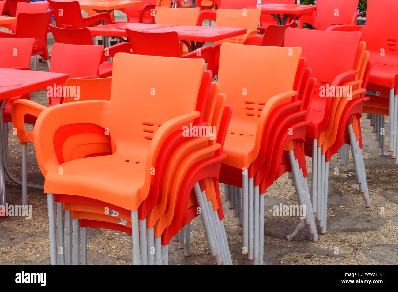 Gruppo di orange sedie vuote di plastica in fila Foto Stock