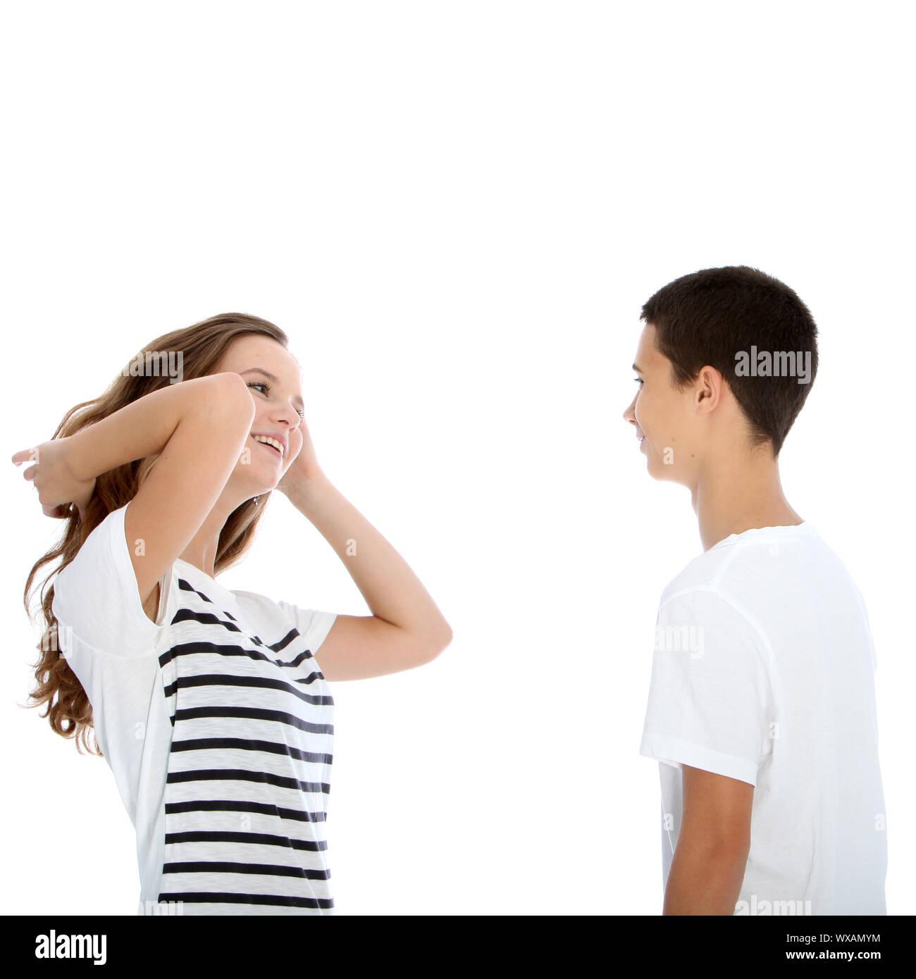 Giovane coppia adolescenti a parlare con la ragazza sfogliare i suoi capelli e ridere flirtaceously isolato su bianco Foto Stock