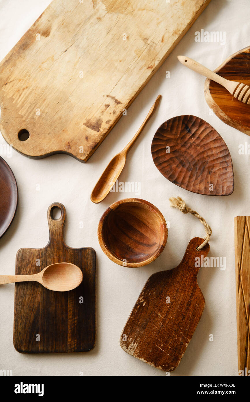 Vari articoli per la tavola in legno. I taglieri, cucchiai di diverse forme, piastra e ciotola sulla tovaglia di lino Foto Stock