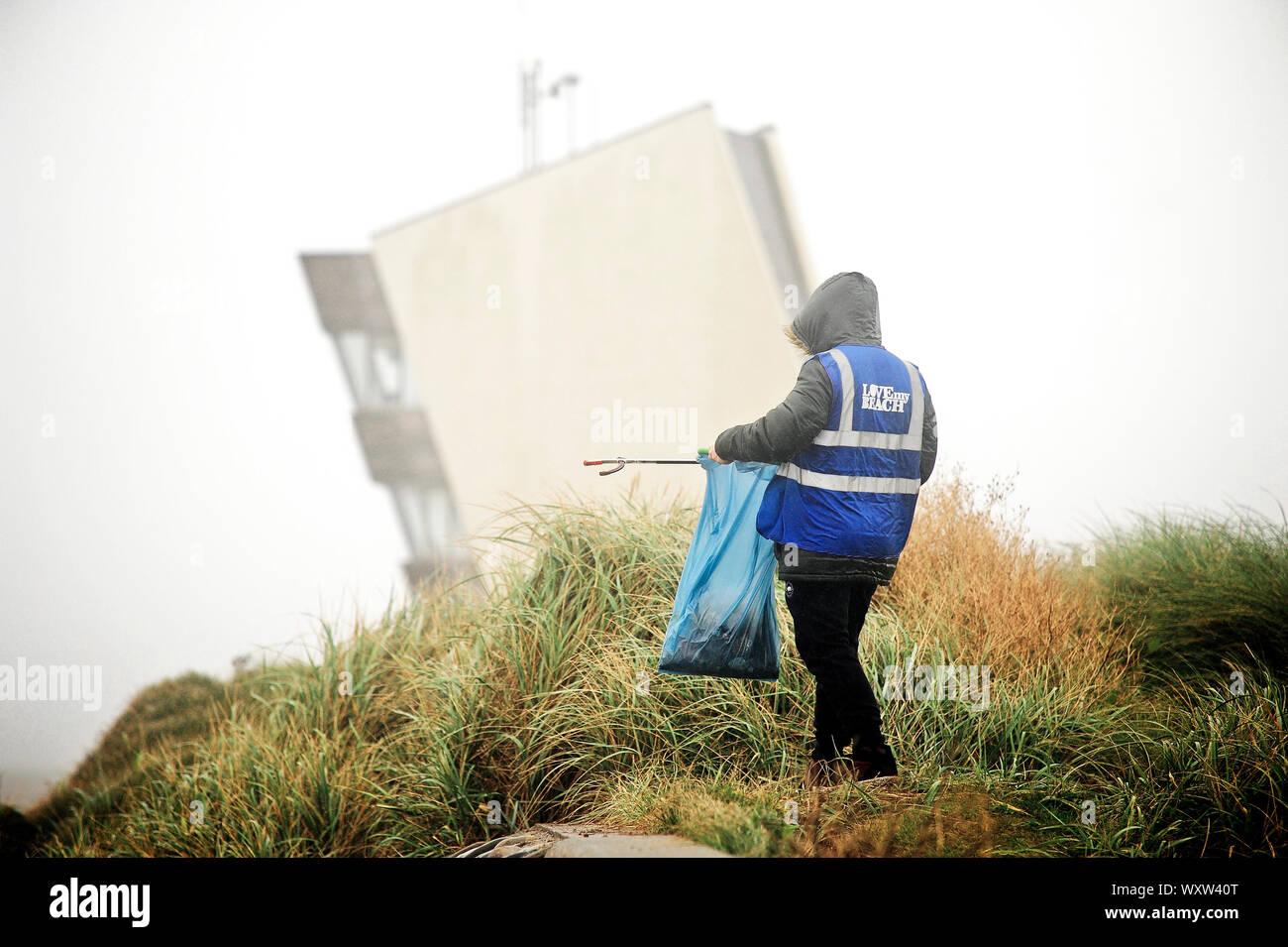 Raccoglitrice solitaria che lavora di fronte alla torre di osservazione di Rossall Point sul lungomare di Fleetwood in condizioni climatiche fredde e umide Foto Stock