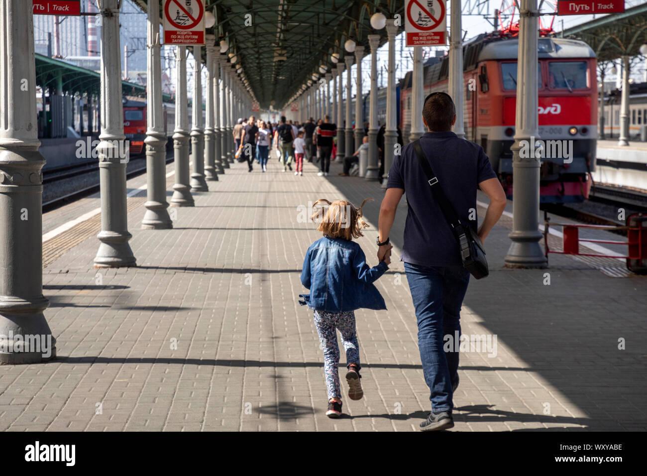 La gente a piedi sulla piattaforma di Mosca Belorussky stazione ferroviaria con treni pendolari e treni a lunga percorrenza a Mosca, Russia Foto Stock