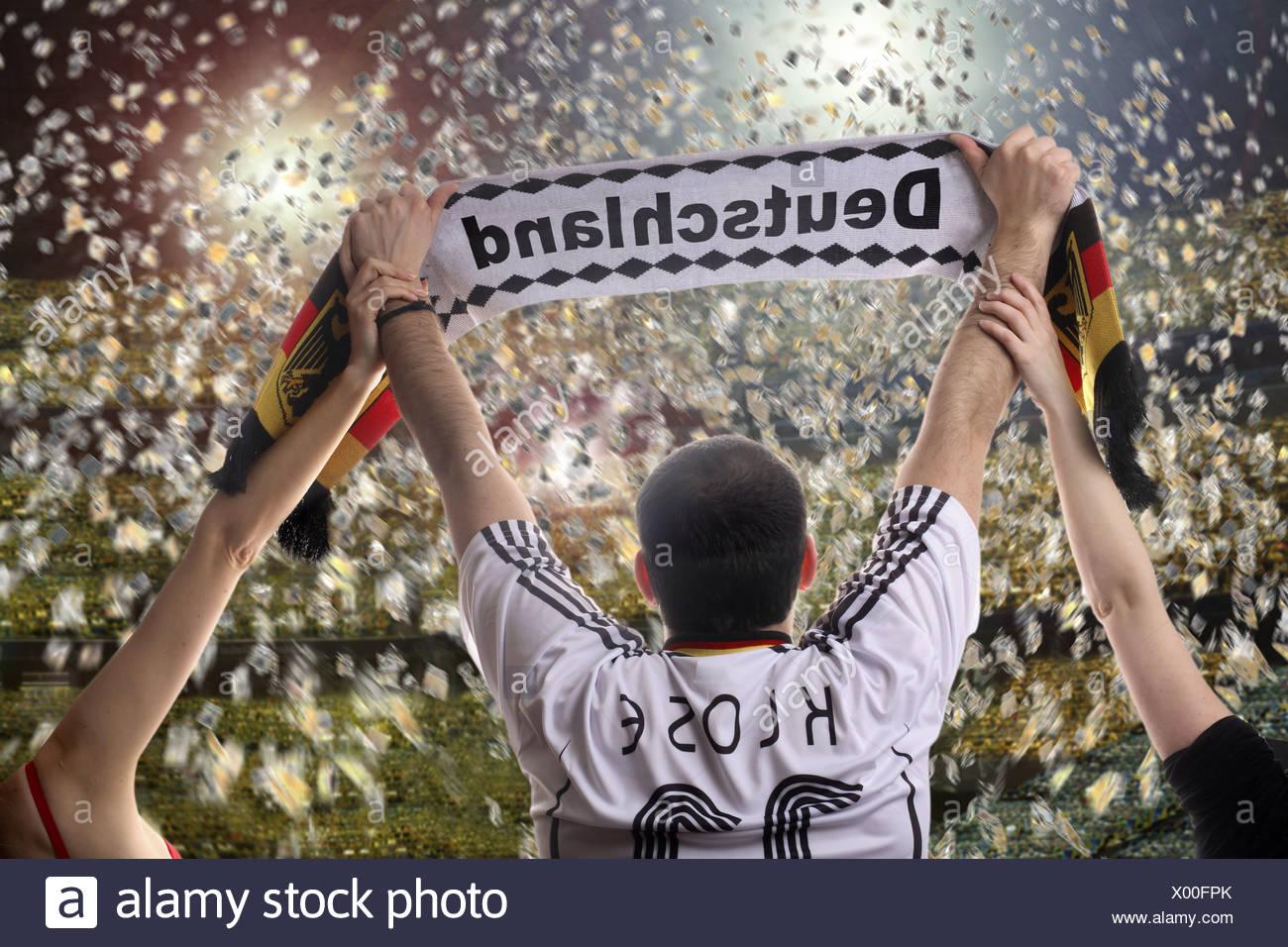 Appassionato di calcio tenendo in mano un tedesco sostenitori sciarpa, visto da dietro con i confetti in uno stadio di calcio Immagini Stock