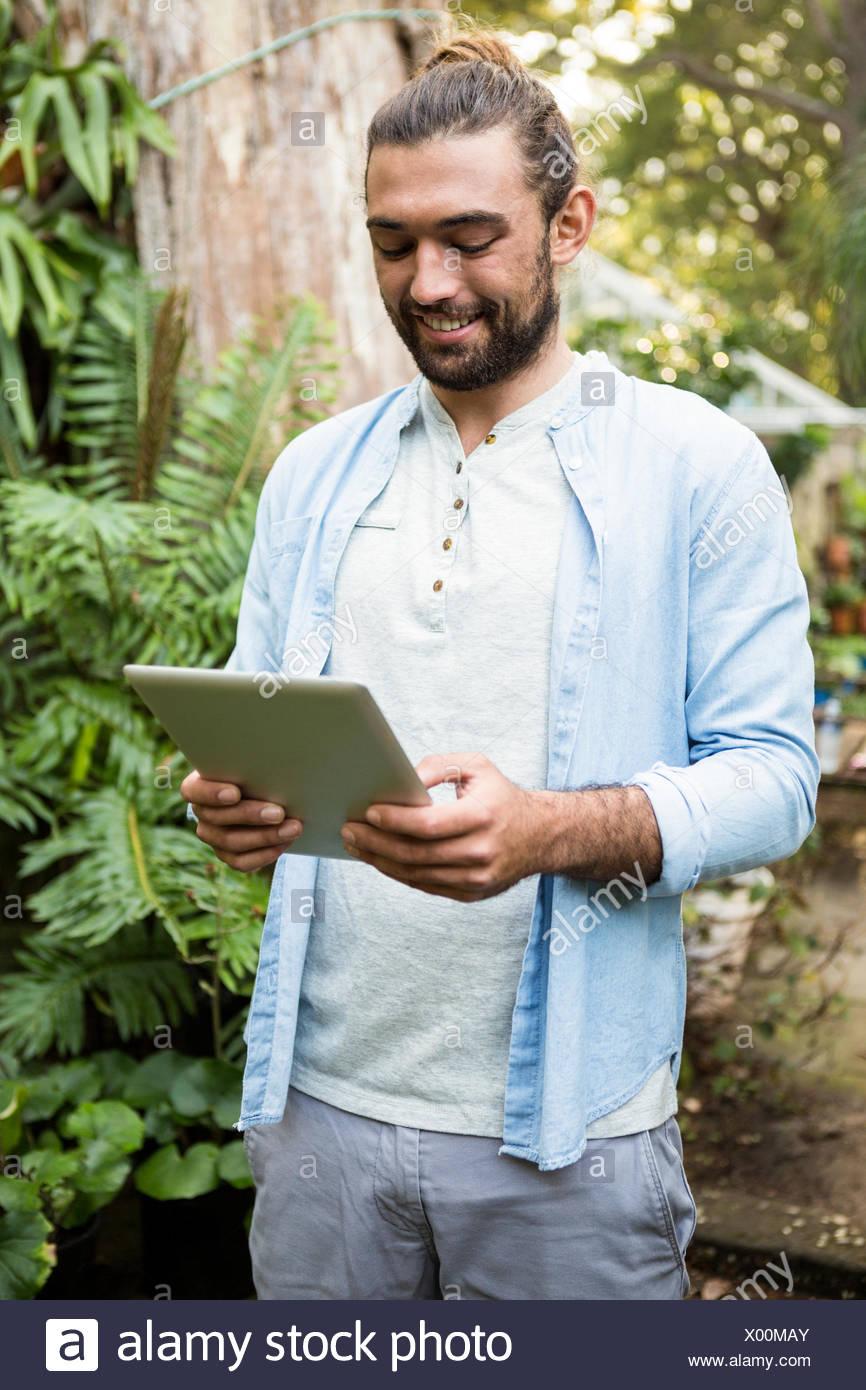 Felice proprietario utilizzando digitale compressa in giardino Immagini Stock
