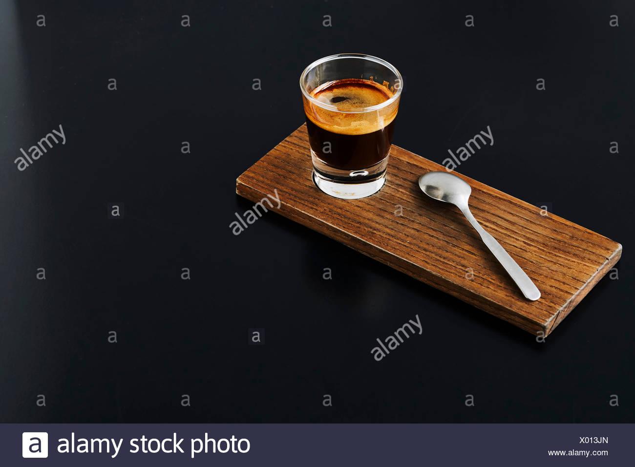 Close-up di un colpo di espresso sul pannello di legno Immagini Stock