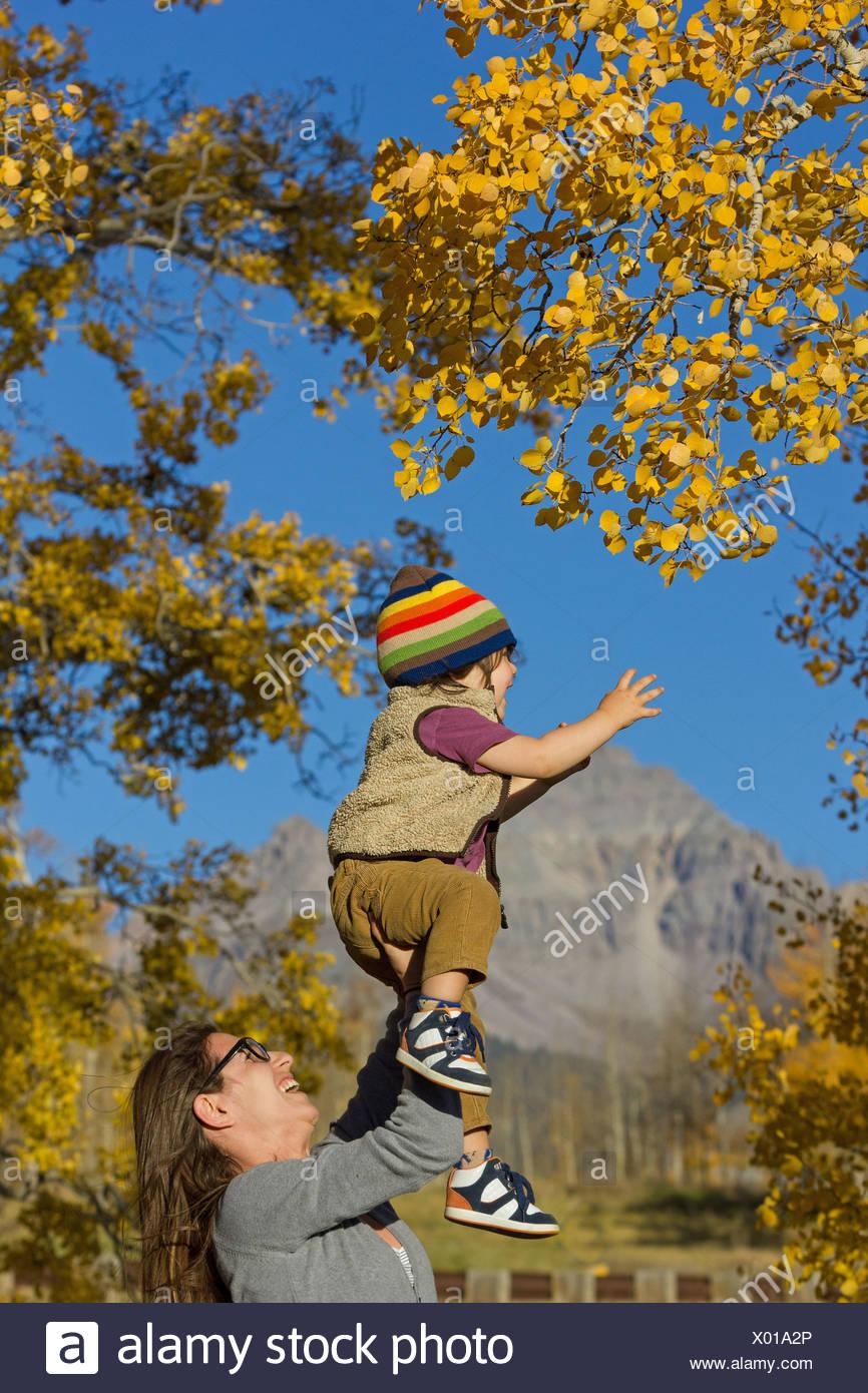 Madre tenendo alto il toddler tra alberi di autunno Immagini Stock