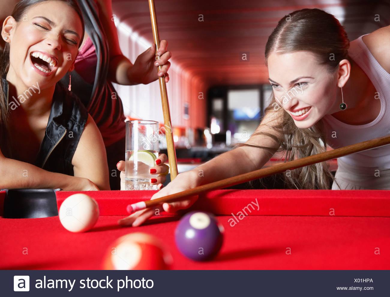 Tre donne giocando a biliardo e ridere Immagini Stock