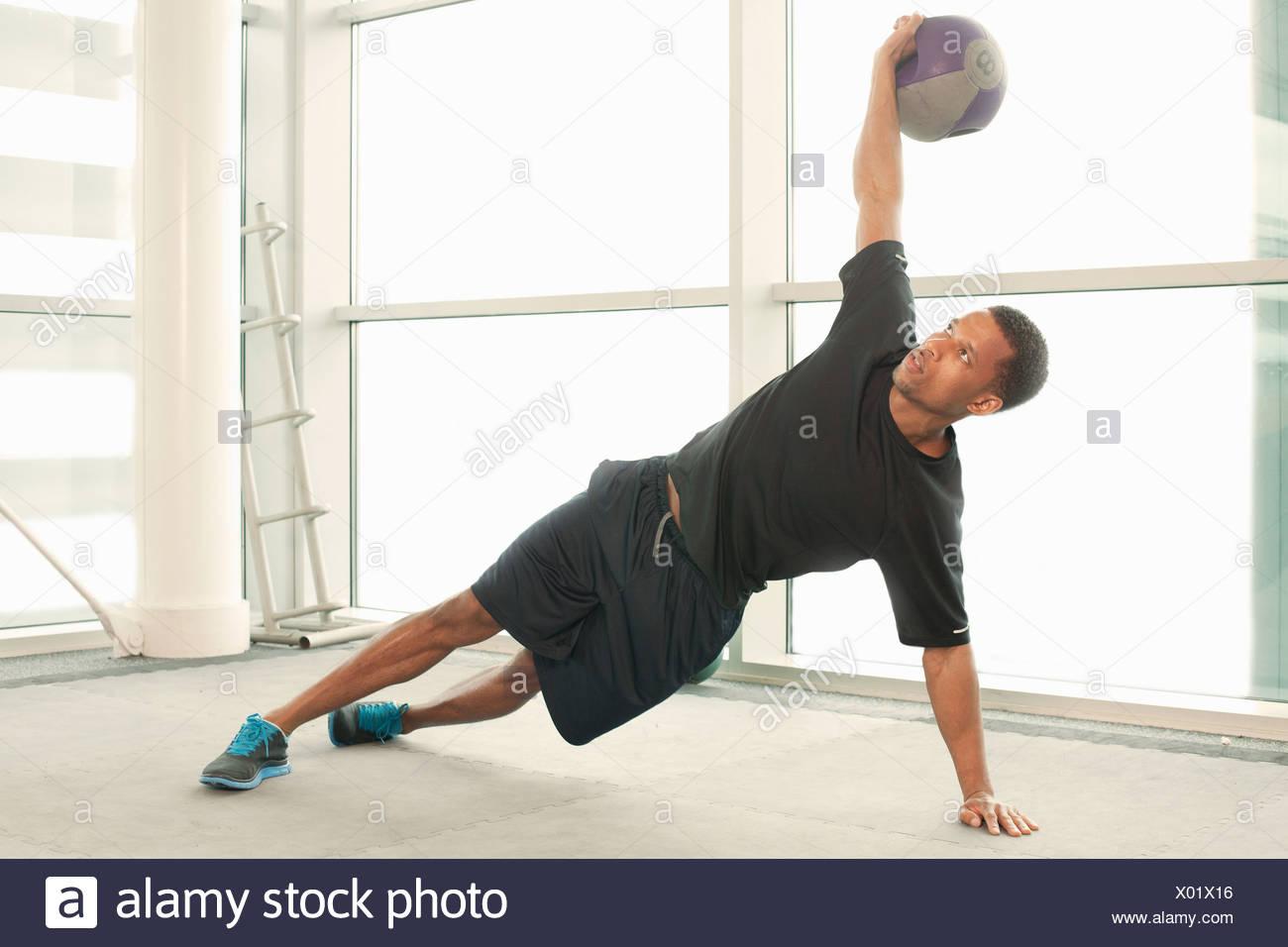 L uomo lo stiramento usando palla ginnica Immagini Stock