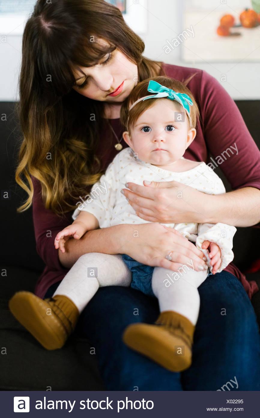 Madre e figlia (12-17 mesi) seduto sul divano Immagini Stock