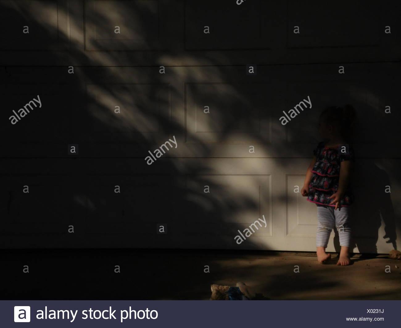 Per tutta la lunghezza della ragazza in piedi contro la parete In Home Immagini Stock