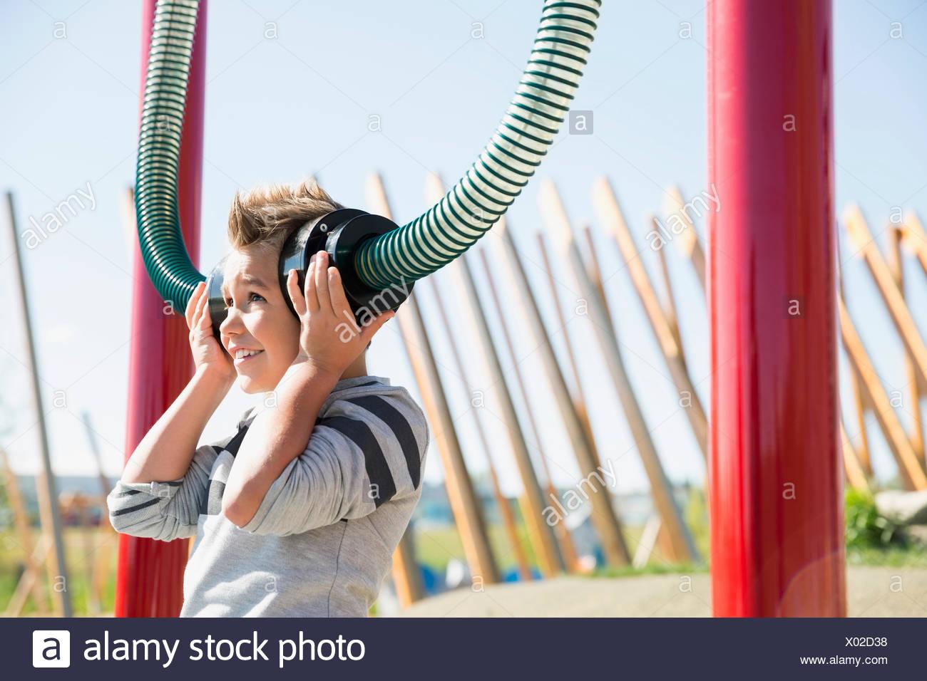 Ragazzo giocando in ascolto per i tubi nel soleggiato parco giochi Immagini Stock