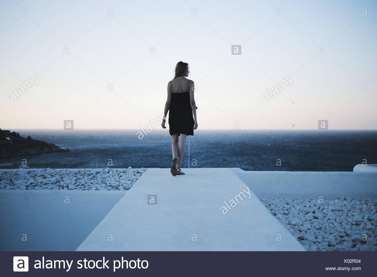 Vista posteriore della donna che guarda al mare Immagini Stock