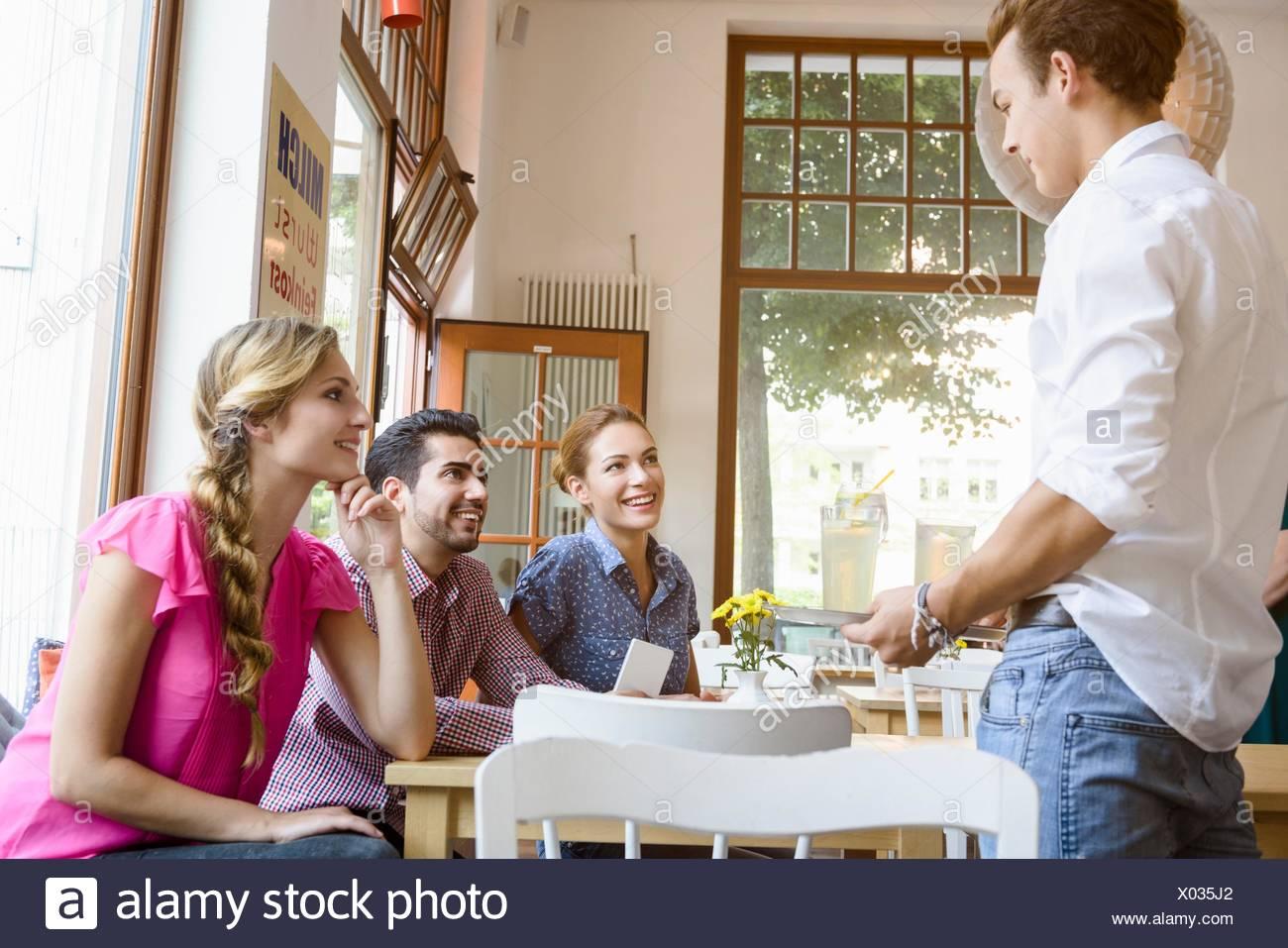 Cameriere facendo ordine da giovani amici adulti in cafe Immagini Stock