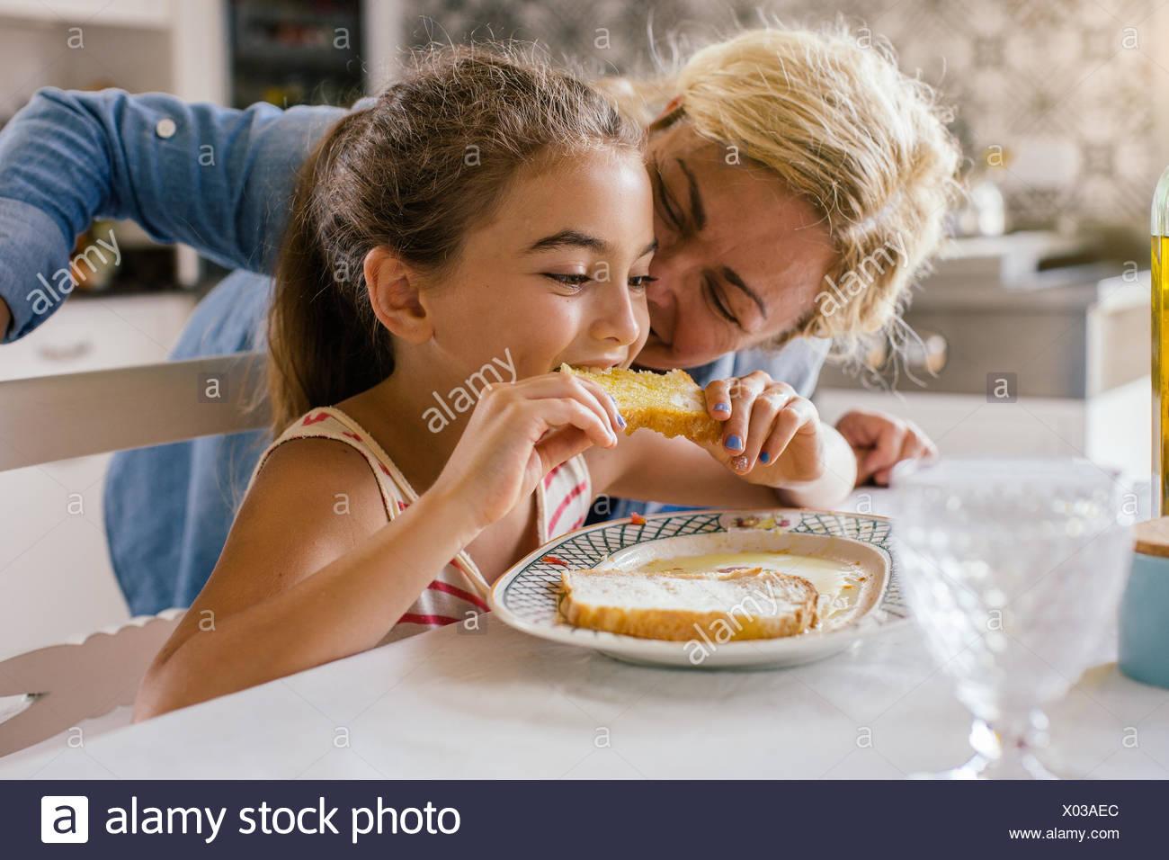 Ragazza di mangiare toast con la nonna Immagini Stock