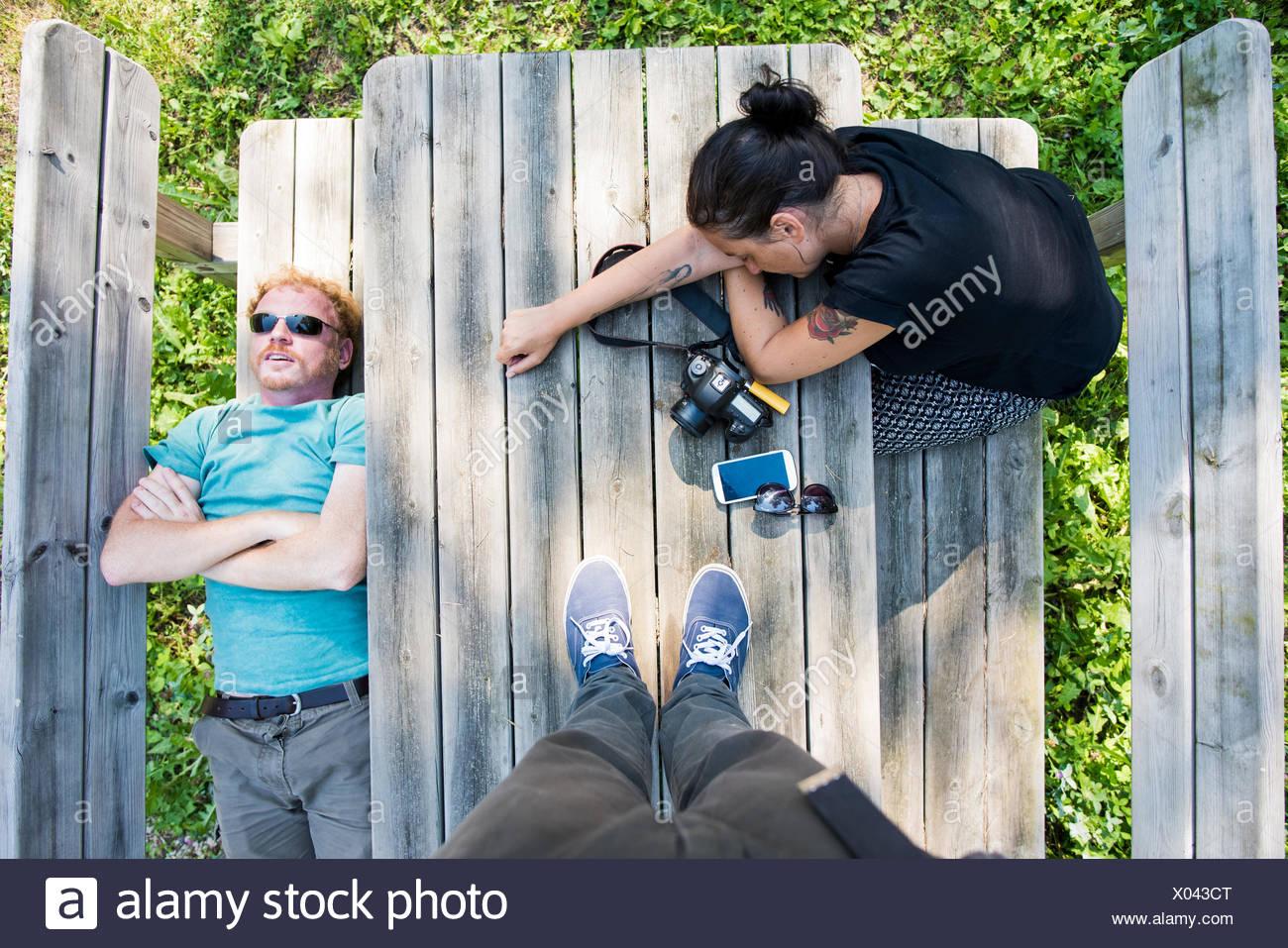 Tettuccio di punto di vista colpo di accoppiarsi in appoggio sul banco per picnic Immagini Stock