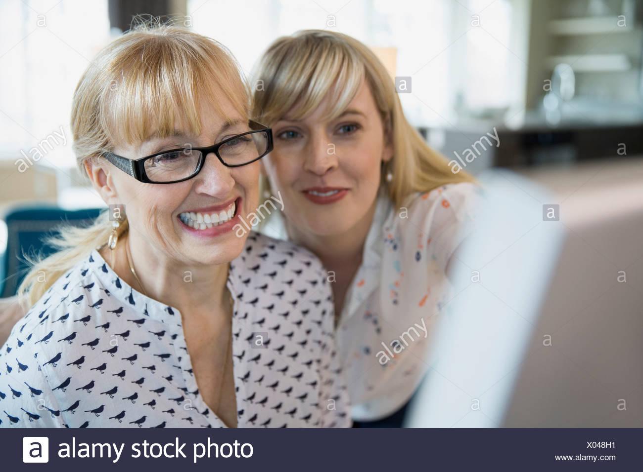 Entusiastico madre e figlia tramite il computer Immagini Stock