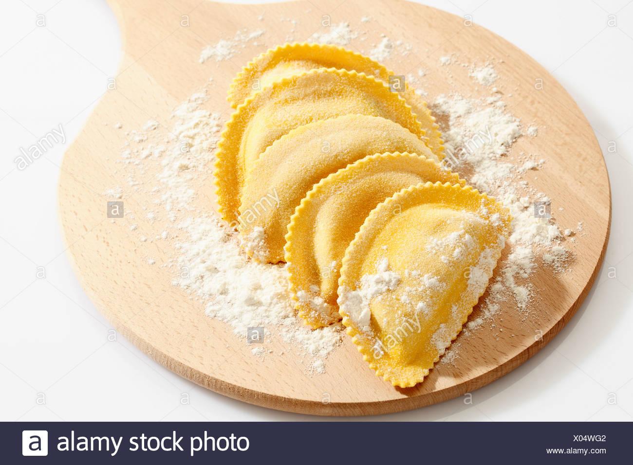 Una mezzaluna la pasta con la farina a fontana sul tagliere Immagini Stock