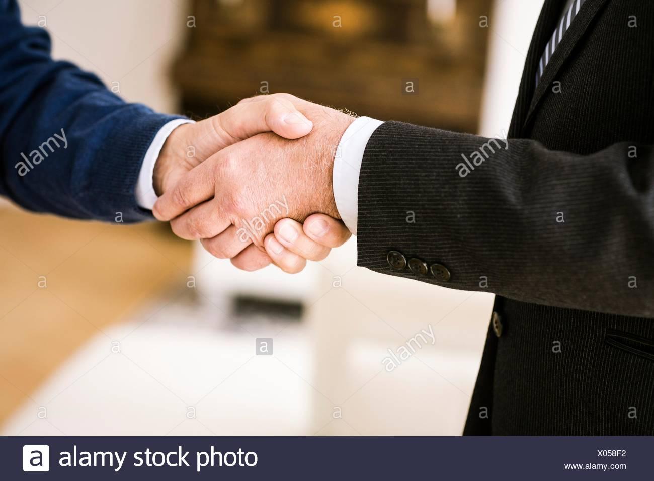 Vista ritagliata di alti uomini stringono le mani Immagini Stock