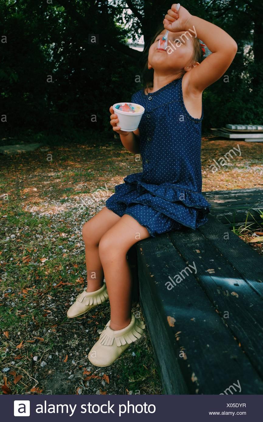 Lunghezza di riempimento di una ragazza avente il gelato in posizione di parcheggio Immagini Stock