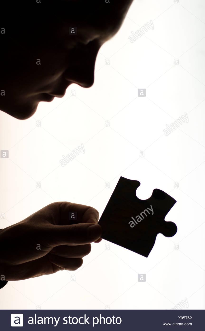 Silhouette di donna holding pezzo del puzzle, vista laterale Immagini Stock
