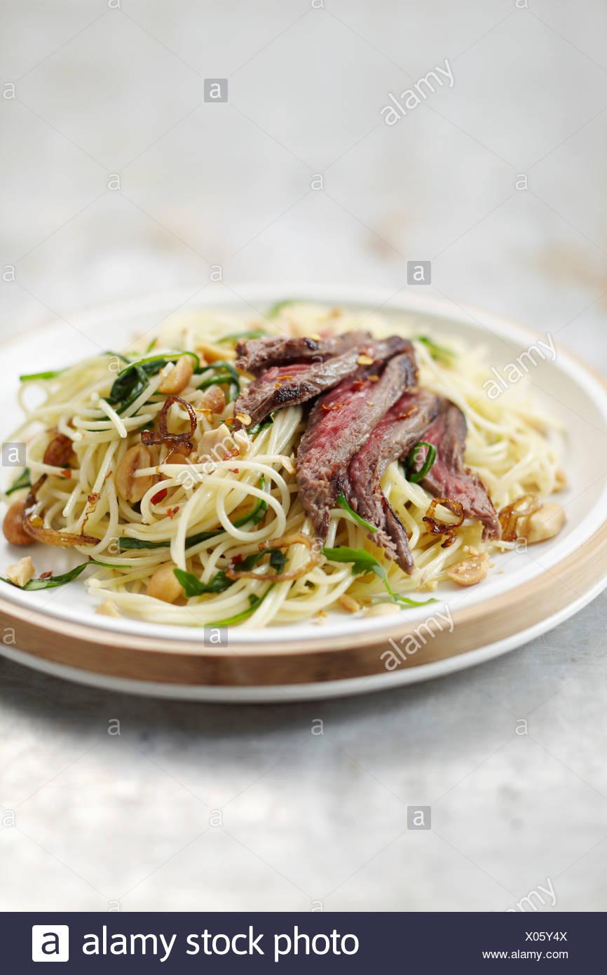 Spaghetti saltati con carne di manzo e di arachidi Immagini Stock