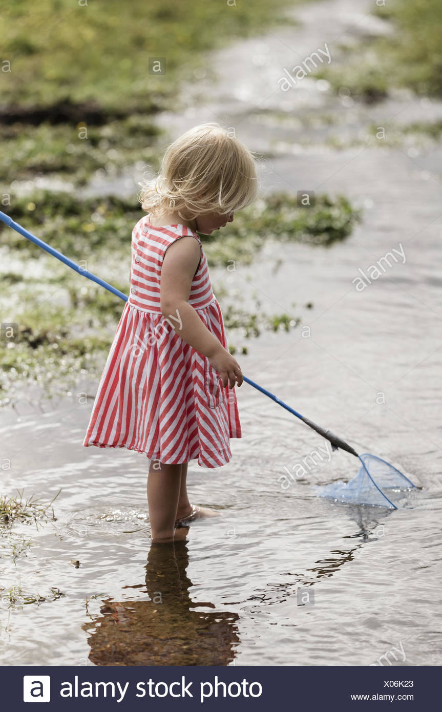Una giovane ragazza che gioca all'esterno. Foto Stock