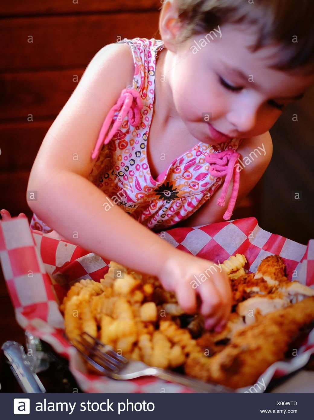 Ragazza carina avente dita di pollo al ristorante Immagini Stock