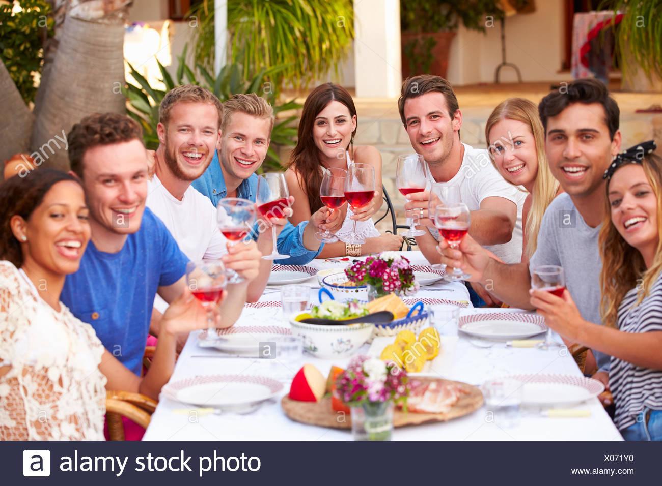 Un folto gruppo di giovani amici gustando pasti all'aperto insieme Immagini Stock