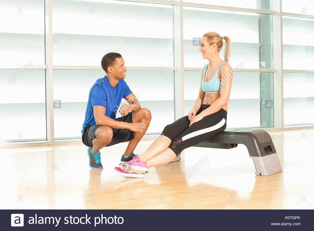 Donna seduta su esercizio passo a parlare con istruttore di fitness Immagini Stock